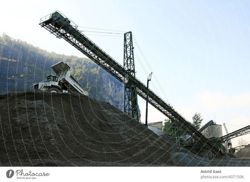 Eine Kiesgrube mit Arbeitsgeräten und LKW im Gebirge kieswerk lkw Industrie förderband Sand bauindustrie firma gebirge baugewerbe kiesgewinnung arbeiten