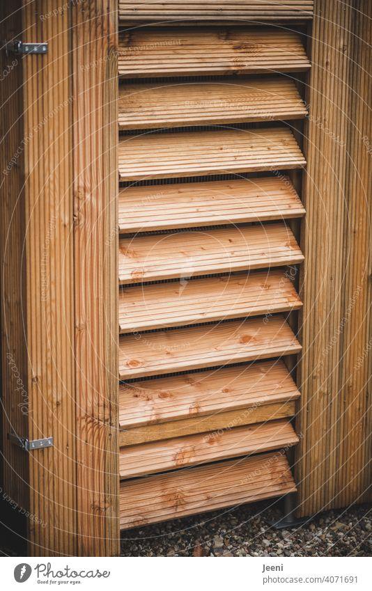 Luftwärmepumpe an einem Einfamilienhaus - verkleidet mit Holz | ökologische, nachhaltige, moderne und umweltfreundliche Heizung Wärmepumpe umweltschonend