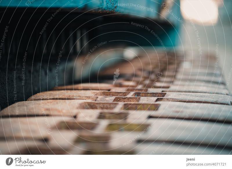 Detailaufnahme der Kette eines Kettenbaggers Kettenglied alt verrostet Kettenglieder Baumaschine Maschine Demontage zerstören Bewegung bewegen Zahnrad abstrakt
