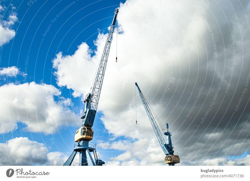 Zwei blau-gelbe Kräne vor wolkigem Himmel in einem Hafen Kran Krane Ladekran Blauer Himmel Wolken Wolkenhimmel Baustelle Bauarbeiten Industrie Hafenkran