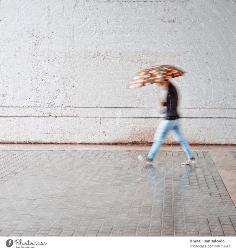 defokussiert Mann mit einem Regenschirm in regnerischen Tagen im Frühling Saison Menschen Person regnet Regentag Wasser menschlich Fußgänger Straße Großstadt