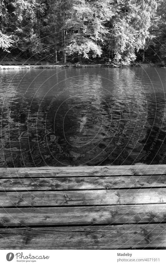 Holzsteg als Badesteg für Badegäste im Sommer bei Sonnenschein am Mittersee in Füssen im Ostallgäu im Freistaat Bayern, fotografiert in klassischem Schwarzweiß