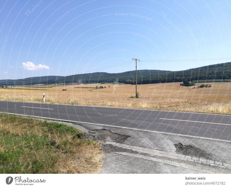 Straßenschäden im Hitzesommer und wüstes Ackerland nach der Ernte Landschaft Ackerbau ländlich Feld Asphalt Mittelstreifen Landstraße niergendwo Bauernhof