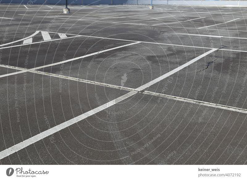 Leerer Stellplatz auf einem Parkplatz mit Fahrbahnmarkierungen Parkplatzsuche leer niemand menschenleer Autofrei Sonntag Corona Shutdown Lockdown geschlossen