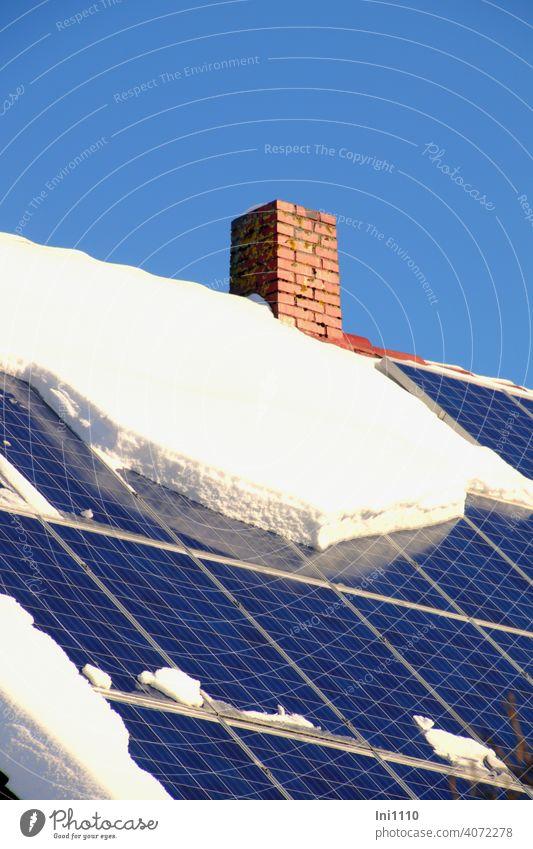 Photovoltaikanlage auf der Dachfläche eines Wohnhauses teilweise mit Schnee bedeckt Solarenergie Stromversorgung Energie Sonnenenergie CO2 Umweltfreundlich