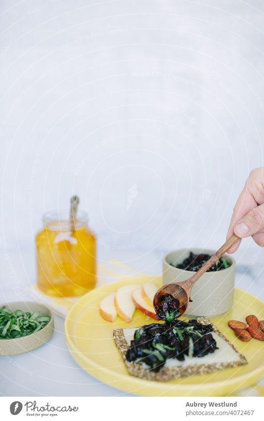 Sommer-Kirsch-Relish-Snack auf einem Körnercracker Mandeln Amuse-Gueule Vorspeisen Äpfel Sortiment Hintergrund Basilikum Beeren Holzplatte Charcuterie