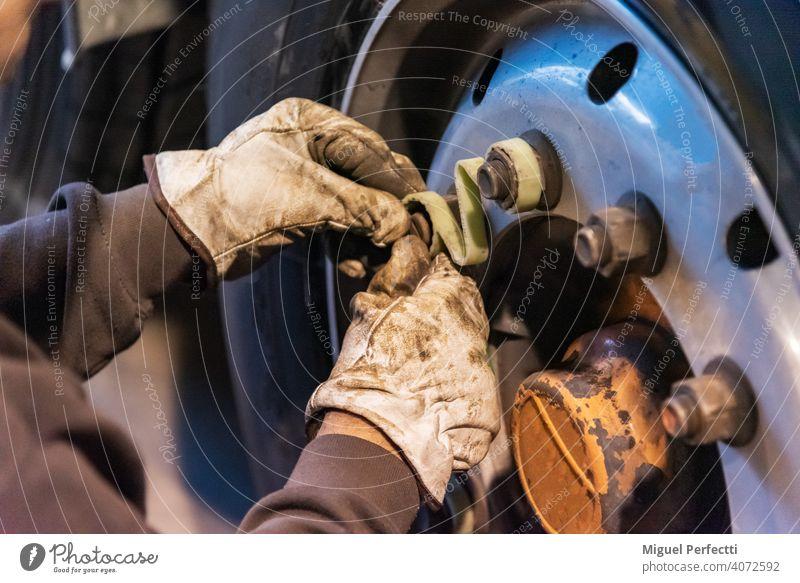 Bediener einer Reifenwerkstatt, der eine Maschine zur Montage oder Demontage eines Lkw-Rads verwendet. Sicherheit Mechaniker Lastwagen Reparatur fixieren Dienst