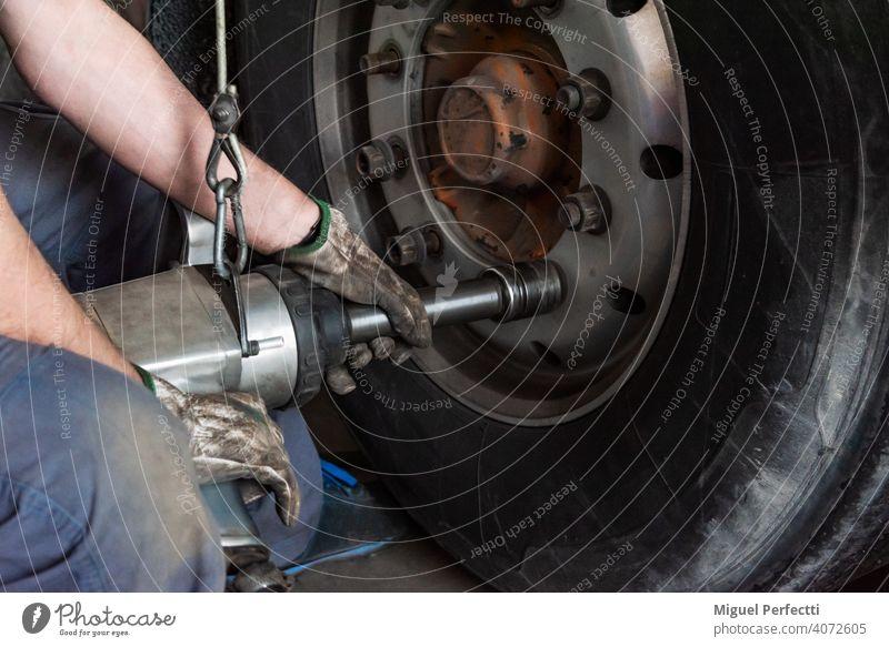 Bediener einer Reifenwerkstatt, der eine Maschine zur Montage oder Demontage eines Lkw-Rads verwendet. Mechaniker Werkzeug Lastwagen Reparatur fixieren Dienst