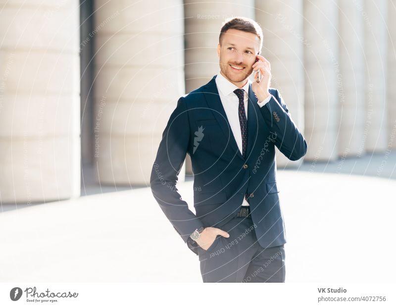 Porträt eines erfolgreichen männlichen Managers, der mit Mobilfunktarifen zufrieden ist, telefoniert, nutzt Bankdienstleister, trägt formalen Anzug, steht in städtischer Umgebung draußen. Professioneller Mann Arbeiter