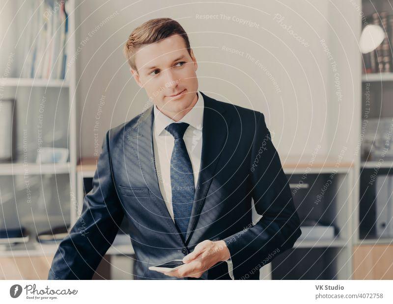 Horizontaler Schuss von gut aussehenden männlichen Manager in stilvoller Kleidung, verwendet Smartphone für die Überprüfung von Informationen über Unternehmertum, liest Nachrichten in Web-Seite, verbunden mit drahtlosen Internet, steht im Büro