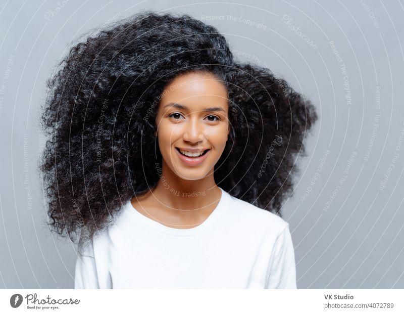 Positive lockige Frau mit natürlicher Schönheit, in weißen lässigen T-Shirt gekleidet, hat glücklichen Ausdruck, schaut direkt in die Kamera, posiert gegen grauen Hintergrund. Fröhliche Teenager-Mädchen drückt gute Gefühle aus