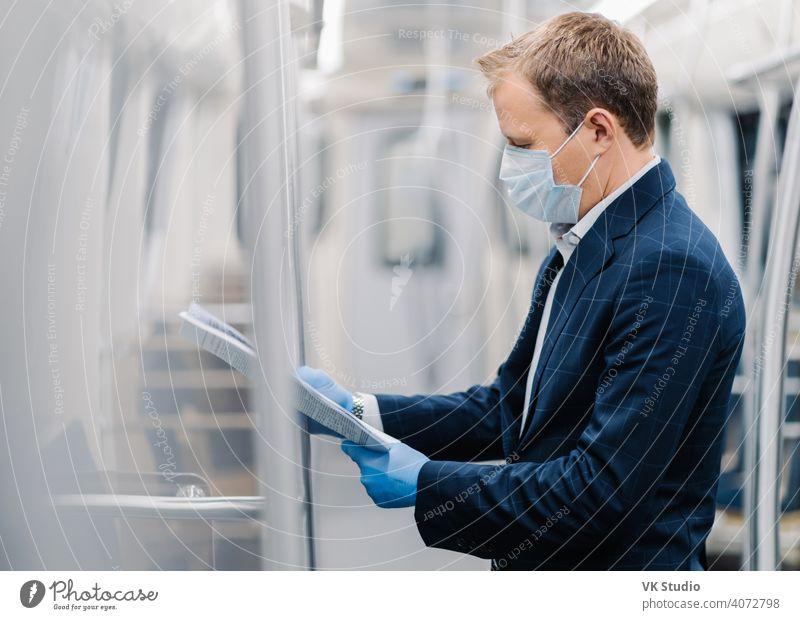 Seitliche Aufnahme eines jungen eleganten Mannes, der aufmerksam Zeitung liest, in einem U-Bahn-Wagen posiert, eine medizinische Maske und Einweg-Gummihandschuhe aus Coronavirus trägt. Soziale Distanzierung, Quarantänemaßnahmen