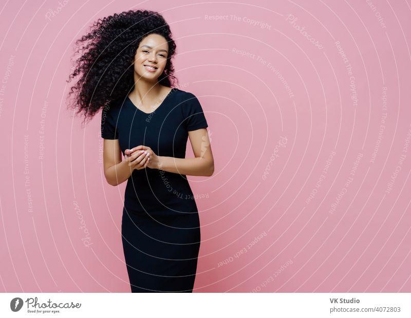 Foto von glücklicher, fröhlicher, dunkelhäutiger, lockiger Frau, die sich für eine lockere Veranstaltung kleidet, positiv lächelt, ein angenehmes Gespräch mit einem Mann genießt, die Hände zusammenhält, im Innenbereich steht, freien Platz für Ihren Text zur Seite