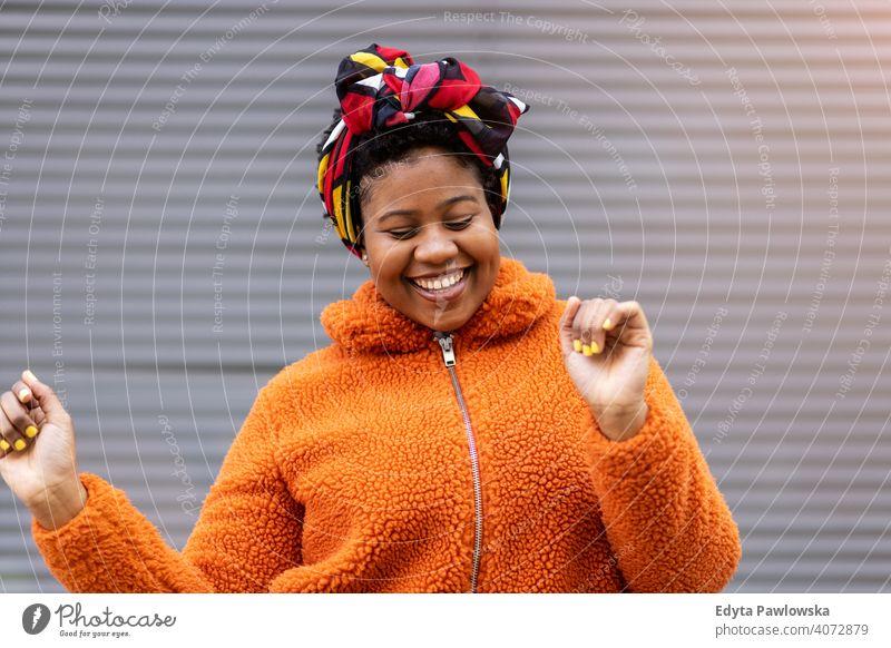 Glückliche junge Frau tanzt vor einer Wand eine Person allein im Freien Tag Positivität selbstbewusst sorgenfrei Menschen Erwachsener lässig schön attraktiv