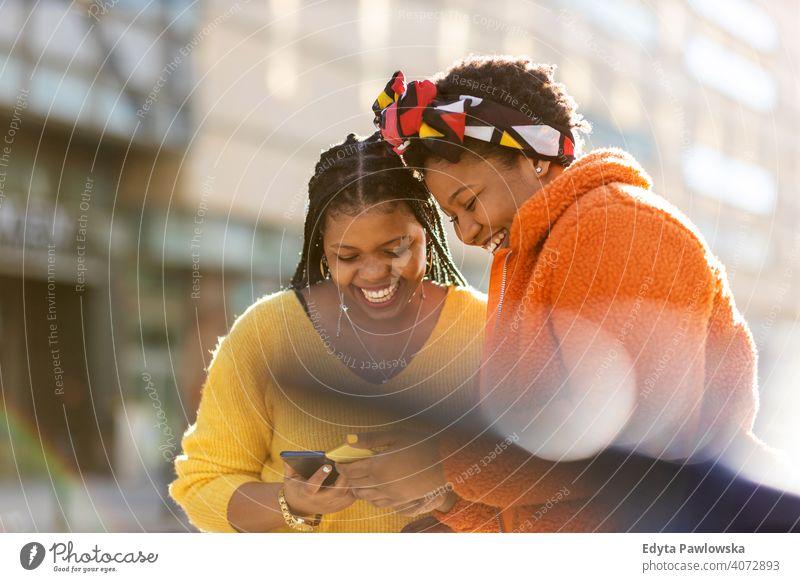 Glückliche Freundinnen, die mit ihren Smartphones in der Stadt Nachrichten versenden Vielfalt unterschiedliche Menschen Liebe im Freien Tag Positivität
