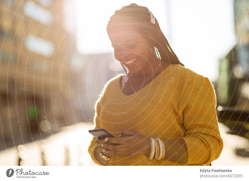 Junge Frau mit Smartphone in einer städtischen Umgebung eine Person allein im Freien Tag Positivität selbstbewusst sorgenfrei Menschen jung Erwachsener lässig