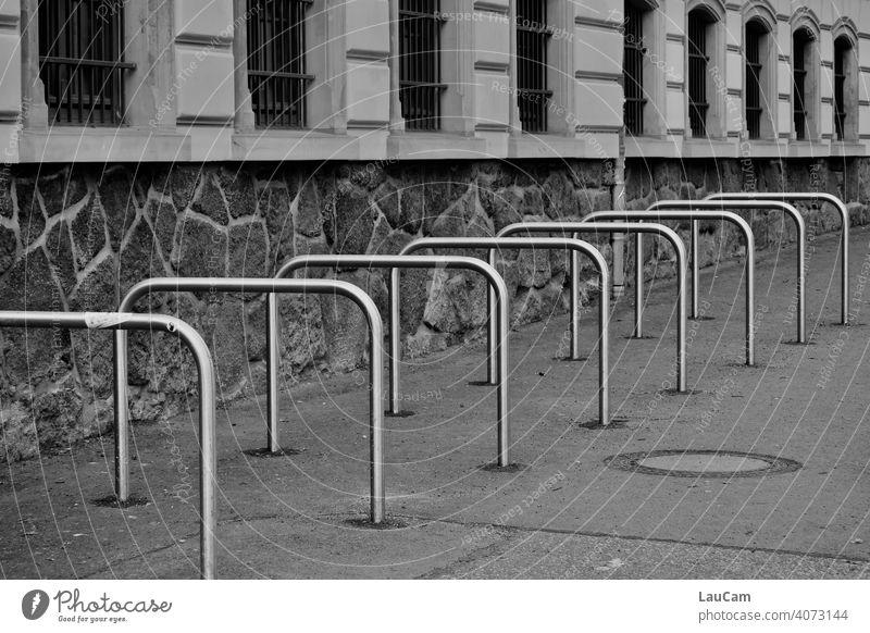 Leere metallene Fahrradständer vor einer Schule in der Corona-Pandemie Fahrradfahren Rad Symmetrie symmetrisch Radständer abstrakt leer Mobilität Leerstand