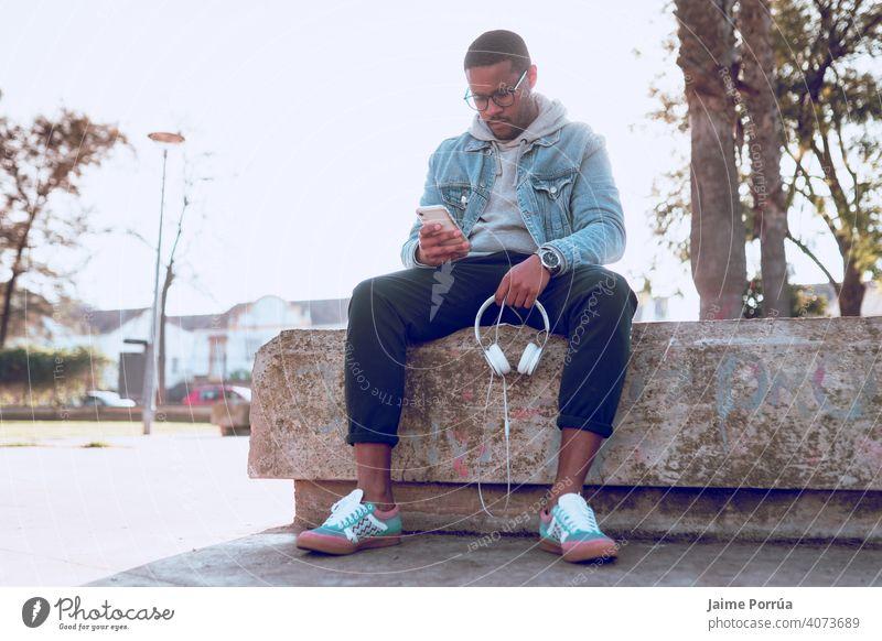 schwarzer Junge sitzt auf einer Bank und hört Musik männlich Kopfhörer hören im Freien allein jung 1 Erwachsener Mann Sitzen Lächeln Menschen