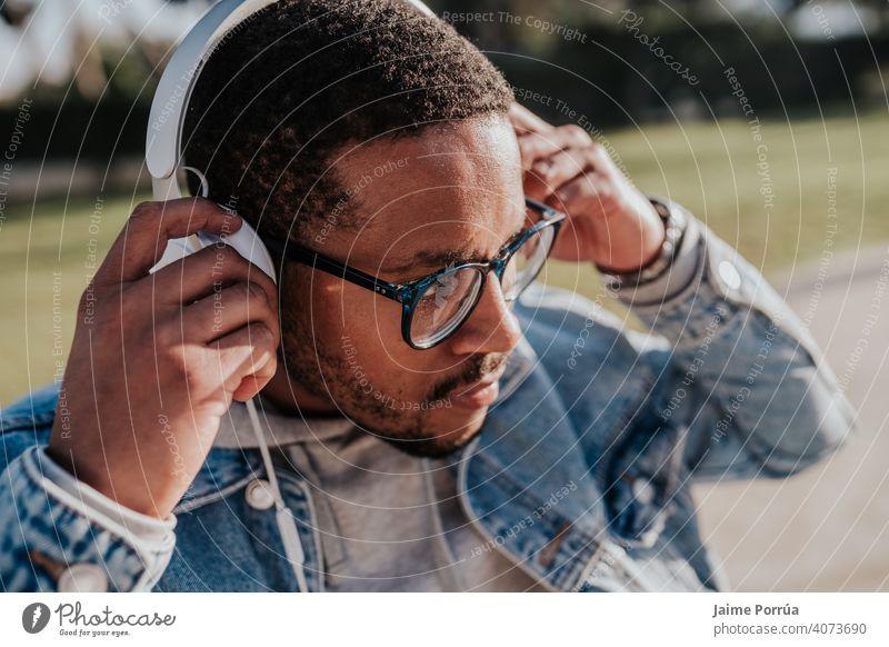 schwarzer Junge im Park, der mit Kopfhörern Musik hört Afro-Look Beteiligung Jugend trendy Teenager Freizeitkleidung Schlittschuh jung Porträt Sonnenuntergang