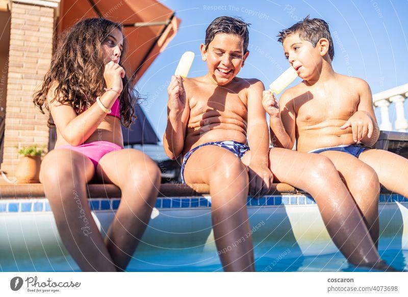 Drei lustige Kinder essen einen Eislutscher Junge Bruder Kaukasier heiter Kindheit Sahne Tochter Tag Latzhose genießen Außenseite Familie Lebensmittel frisch