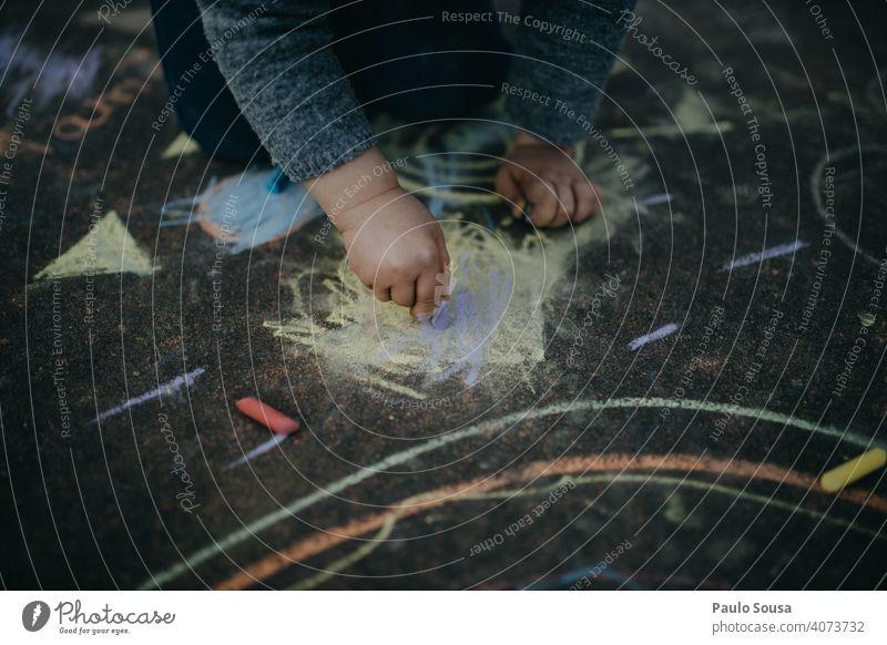 Kind zeichnet mit farbiger Kreide auf dem Boden Nahaufnahme Kindheit zeichnen Zeichnung Kreidezeichnung Gemälde Spielen Kreativität Straße Kunst Farbfoto