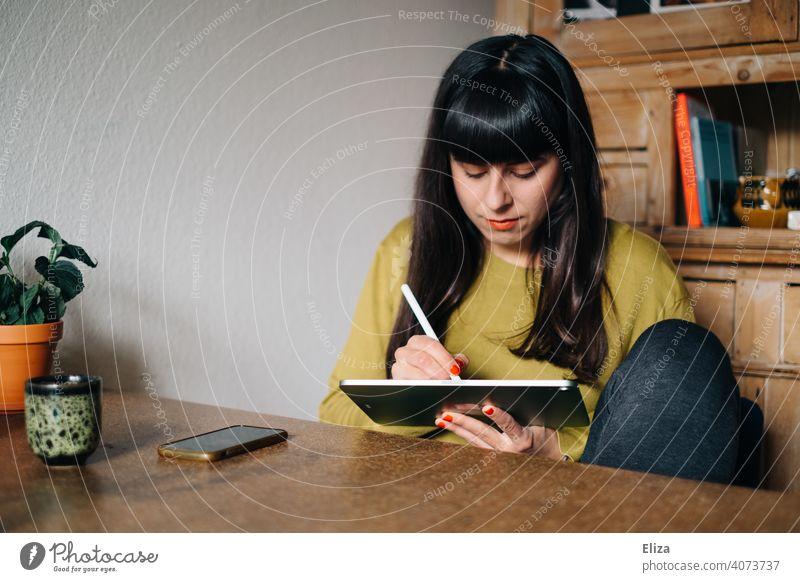 Eine Frau sitzt am Tisch und zeichnet oder schreibt etwas auf einem Tablet malen schreiben zeichnen Stift ipad Apple Pen Kreativität digital Grafikerin