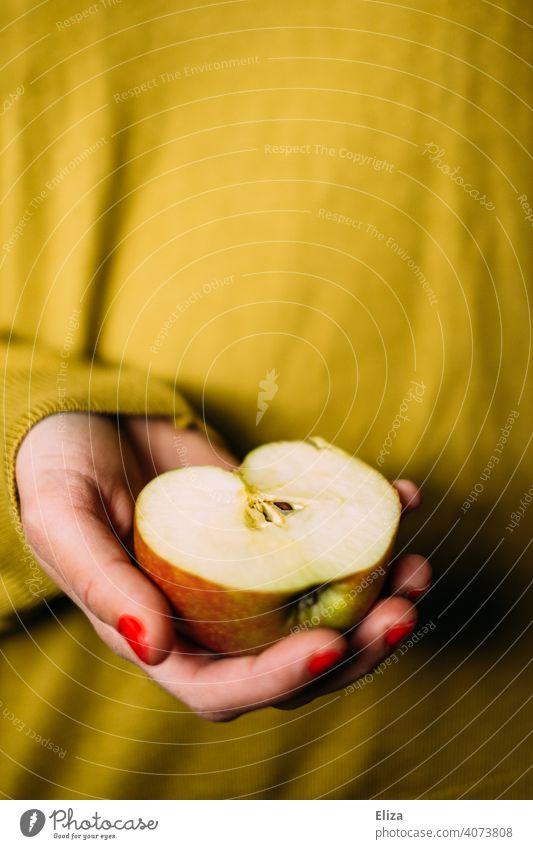 Eine Frau hält eine Apfelhäfte in der Hand Hälfte Apfelhälfte halb Obst gesund Schneewittchen Snack gelb halten lecker Ernährung Gesunde Ernährung