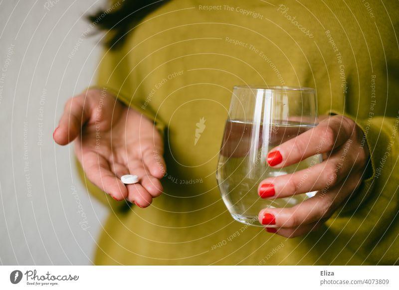 Eine Frau hält eine Tablette und ein Wasserglas in den Händen. Medikament einnehmen. Kopfschmerztablette Ibuprofen Gesundheit Krankheit Schmerztablette