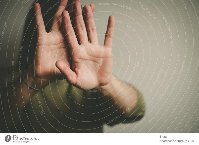 Person hält abwehrend die Hände vor das Gesicht Gewalt schützen Defensive gefährlich bedrohlich verteidigen Angst ablehnen Frau Opfer Mensch häusliche gewalt