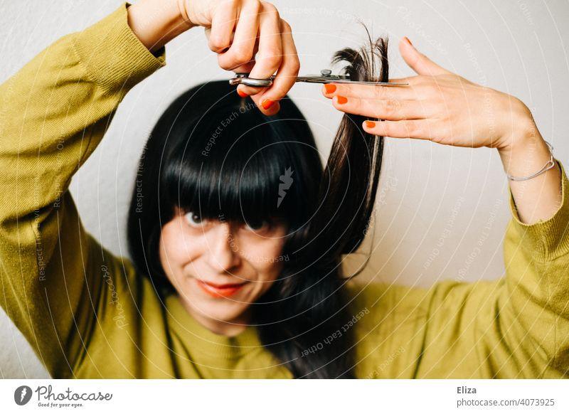 Eine braunhaarige Frau schneidet sich selber die Haare Haarschnitt schneiden Haare schneiden selber machen zuhause dunkelhaarig nachschneiden Lockdown DIY