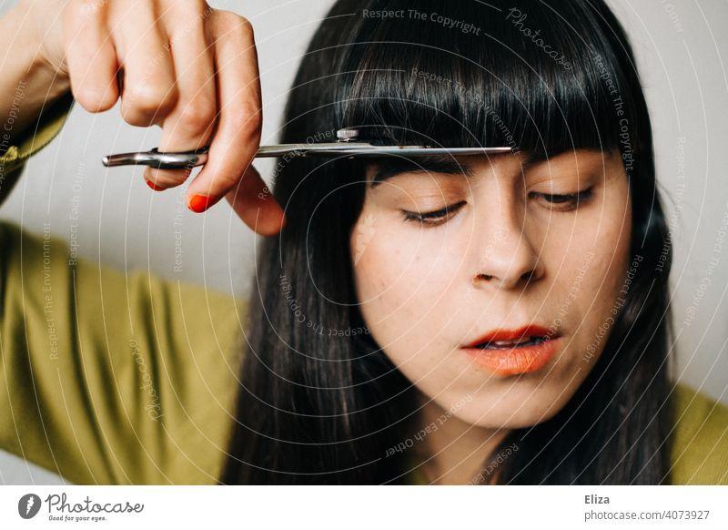 Eine dunkelhaarige Frau schneidet sich Zuhause selber die Haare Haare schneiden zuhause Pony Pony schneiden Schere nachschneiden Haare & Frisuren Friseurin DIY