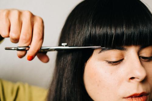 Frau schneit sich selber den Pony nach Haare schneiden Pony schneiden Haarschnitt Lockdown selber machen DIY Friseurin nachschneiden Haare & Frisuren Schere