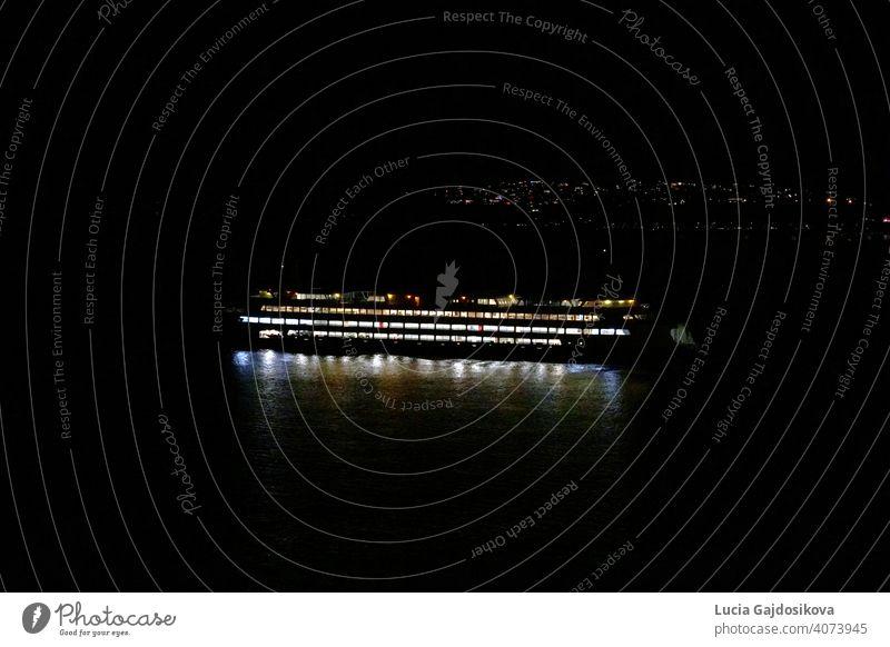 Die Seattle-Bainbridge-Fähre beleuchtet von Kabine und Navigationslichter ist in der Nacht zwischen Seattle und Bainbridge Island, Washington über Puget Sound vorbei. Im Hintergrund sind Lichter der Vororte von Seattle mit viel Kopierraum.