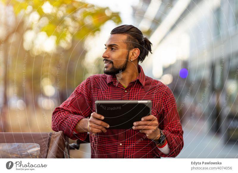 Junger Mann verwendet digitales Tablet im Freien in städtischer Umgebung Singhalesisch asiatisch Inder bärtig außerhalb Straße urban Stehen Großstadt Warschau