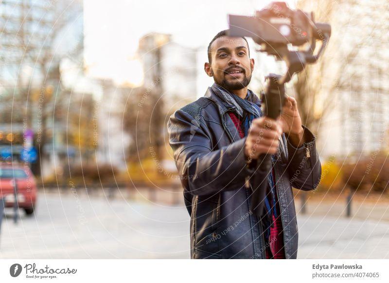 Mann filmt einen Vlog mit Kamera in der Stadt Video Blogger Vlogger Journalist Influencer Fotograf Technik & Technologie Fotokamera reisen Tourist Entdecker
