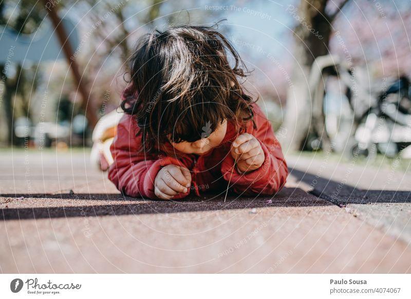Nettes Mädchen, das sich auf den Boden legt und ein Insekt beobachtet Kind Kindheit Kaukasier 1-3 Jahre Spielen Neugier Freizeit & Hobby niedlich