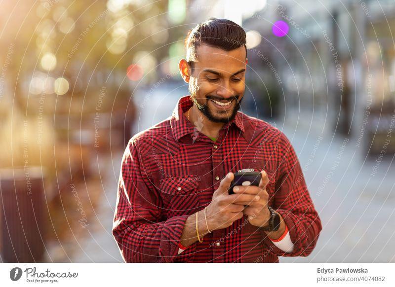 Junger Mann, der auf der Straße geht und Textnachrichten schreibt Singhalesisch asiatisch Inder bärtig außerhalb urban Stehen im Freien Großstadt Warschau eine