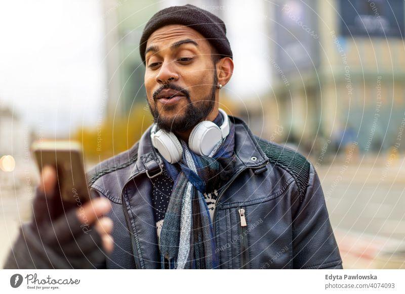 Hübscher junger Mann mit Handy auf der Straße Singhalesisch asiatisch Inder bärtig außerhalb urban Stehen im Freien Großstadt Warschau eine lässig Lifestyle Typ
