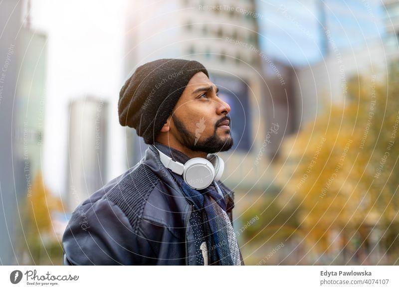 Porträt eines stilvollen jungen Mannes in einer Stadt Straße stehen Singhalesisch asiatisch Inder bärtig außerhalb urban Stehen im Freien Großstadt Warschau