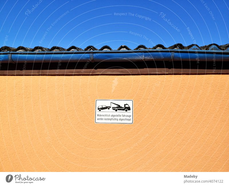 Hinweisschild für Falschparker an einer Fassade in Apricot bei blauem Himmel und Sonnenschein im Sommer in Oerlinghausen bei Bielefeld am Hermannsweg im Teutoburger Wald in Ostwestfalen-Lippe