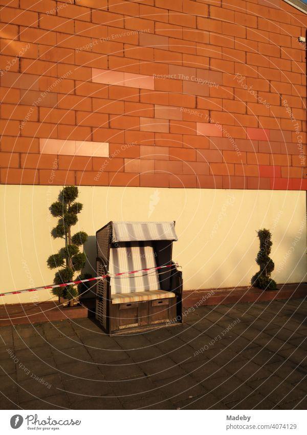 Strandkorb mit Absperrband wegen Corona mit skurril geformten Pflanzen vor Hauswand in Naturfarben im Licht der untergehenden Sonne in Oerlinghausen bei Bielefeld am Hermannsweg im Teutoburger Wald in Ostwestfalen-Lippe