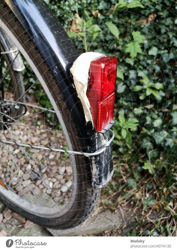 Mit Klebeband fixiertes rotes Rücklicht an schwarzem Schutzblech an einem Fahrrad vor grüner Hecke in Oerlinghausen bei Bielefeld am Hermannsweg im Teutoburger Wald in Ostwestfalen-Lippe