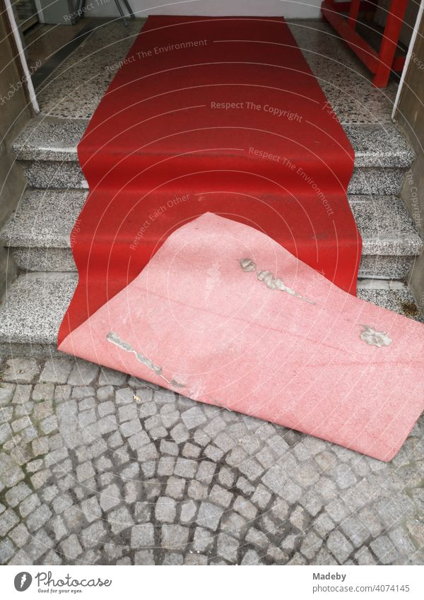 Roter verwehter Teppich auf alten grauen Treppenstufen und grauem Kopfsteinplflaster am Eingang eines Friseur in der Altstadt von Oerlinghausen bei Bielefeld am Hermannsweg im Teutoburger Wald in Ostwestfalen-Lippe