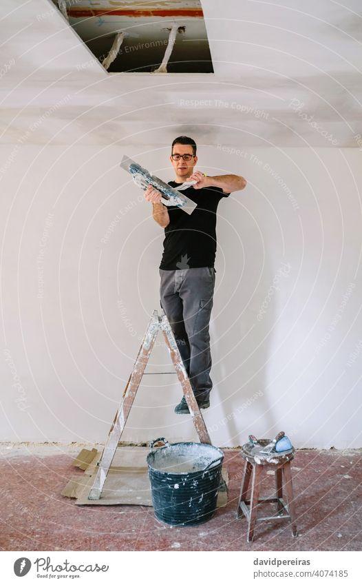 Baumeister beim Putzen mit Spachtel Maurer Bauherr Gipser abholend Gipsputz verputzen Kelle auf die Leiter geklettert arbeiten heimwerken Reform Haus