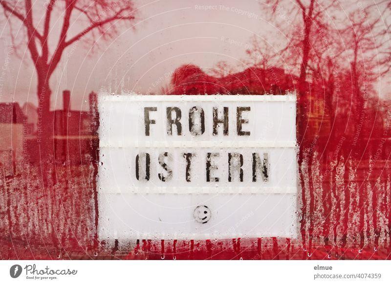 FROHE OSTERN und ein Smiley sind hinter einer angelaufenen Scheibe mit rotem Hintergrund auf einem Schild zu erkennen Ostern Frohe Ostern ins Wasser fallen