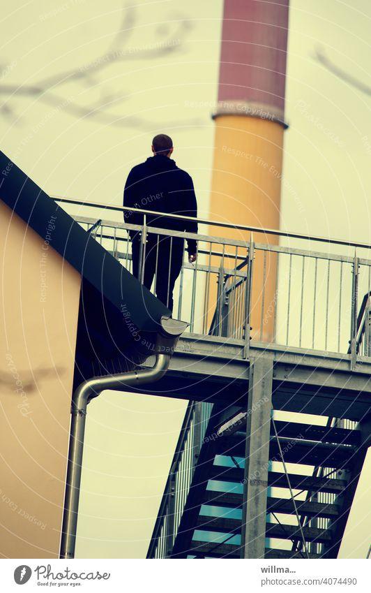 RAUCHPAUSE Mensch Person stehen Geländer Rückansicht Treppe Schornstein schief schiefes Weltbild Mann Eisentreppe Blick in die Zukunft Klimawandel nachdenken