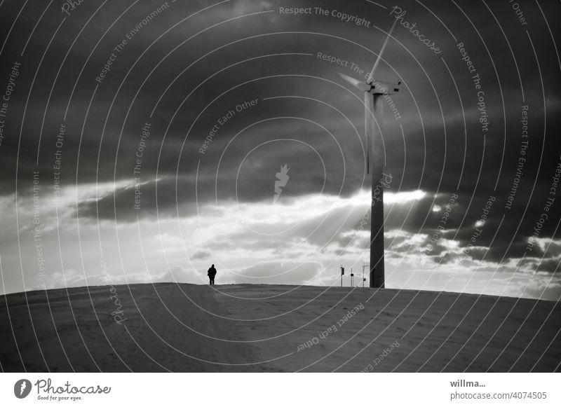 Energie-Tankstelle Windrad dunkle Wolken Sonnenstrahlen winziger Mensch klein Windenergie Energie tanken Erneuerbare Energie Windkraftanlage Energiewirtschaft