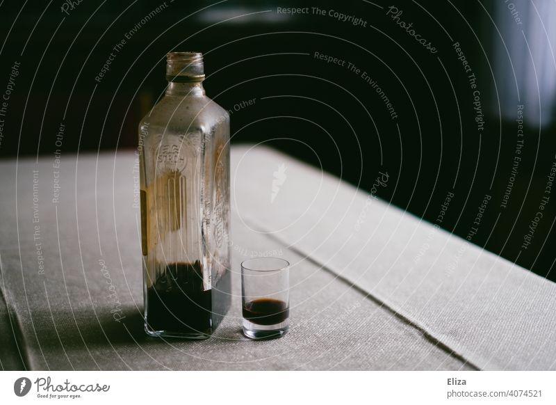 Schnapsflasche gefüllt mit Alkohol steht neben Schnapsglas auf einem Tisch Flasche trinken Alkoholsucht hochprozentig Einsamkeit Spirituosen Rauschmittel
