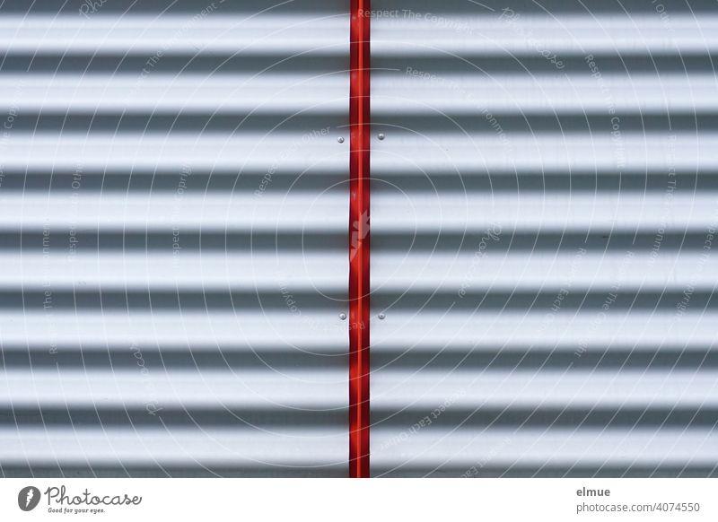 graue Wellblechplatte durch deren Mitte ein roter Streifen verläuft / Sichtschutz / halbieren Hälfte gestreift Blech Metall Platte Blechwand Strukturen & Formen
