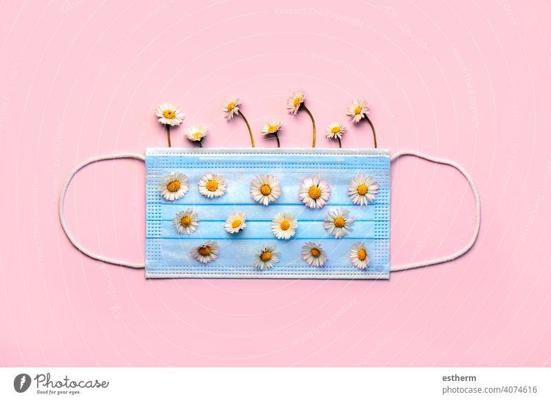 Chirurgische Schutzmaske mit weißen Gänseblümchenblüten, Konzept einer Frühjahrsallergie Coronavirus Operationsmaske Allergie medizinische Gesichtsmasken Virus